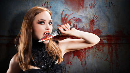 sexy devil: female vampire with a knife in front of a bloody wall Stock Photo