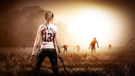 scene like in a horror movie with a woman holding a machete and a knife and standing on a field with approaching zombies Stockfoto