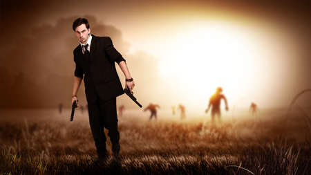 monster movie: cool man in a suit holding guns, standing on a field with many zombies behind him Stock Photo