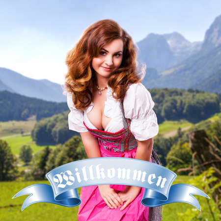 willkommen: attractive young girl in a dirndl and a badge stating welcome in German