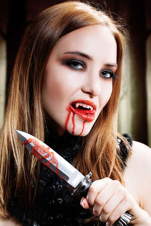 gothic woman: attractive vampire with a bloody knife
