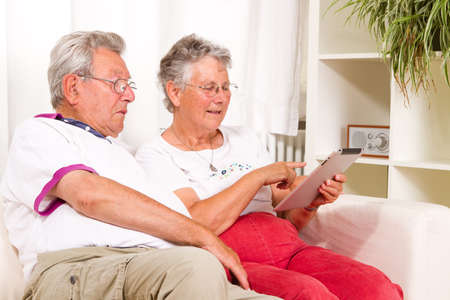 old sofa: senior couple with a tablet computer Stock Photo