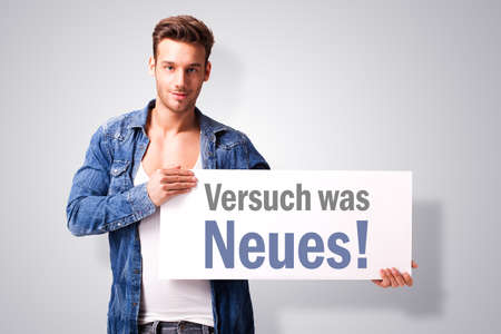 try: handsome young man with a signboard stating try something new in German