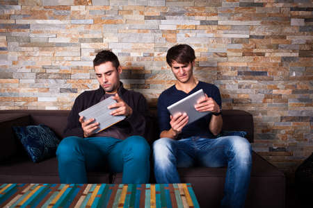 computer game: two friends playing together with tablet computers Stock Photo