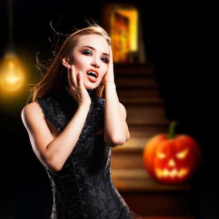 attractive vampire in a dark lit cellar photo