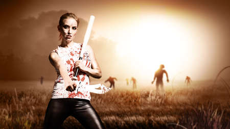 scene like in a horror movie with a woman holding a machete and a knife and standing on a field with approaching zombies Stock Photo