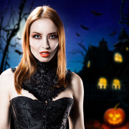 sexy halloween girl: attractive vampire in front of a halloween house
