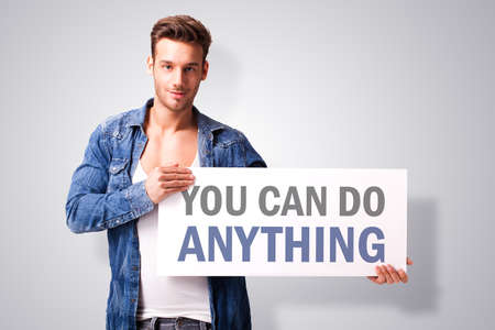 stating: handsome young man with a signboard stating \you can do anything\ Stock Photo