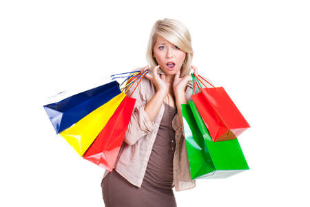 bargain hunting: surprised young woman with many shopping bags on isolated background