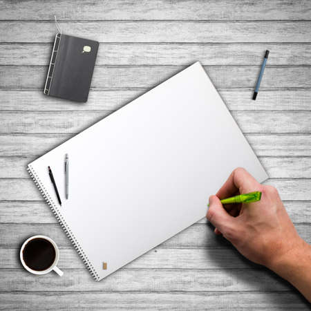 hand ready to write on a blank paper block photo