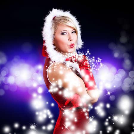 young miss santa blowing snow Stock Photo