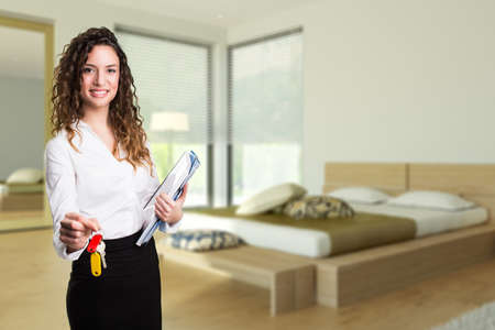accommodation: attractive businesswoman handing over keys to an apartment