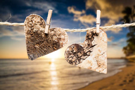 passion couple: two hearts on a line in front of a tropical beach Stock Photo