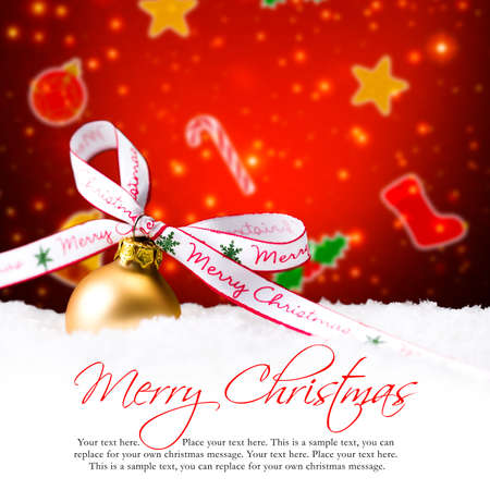 christmas greetings: golden christmas ball in the snow with merry christmas bow and sample text Stock Photo