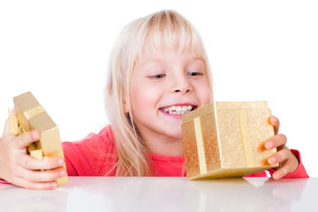 adorable young smiling girl looking into a golden gift box Stock Photo