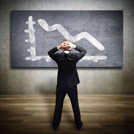contabilidad financiera: hombre de negocios mirando sorprendido a un diagrama de la caída Foto de archivo