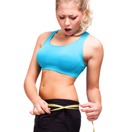 dismayed: attractive blond woman looking shocked at her measure tape