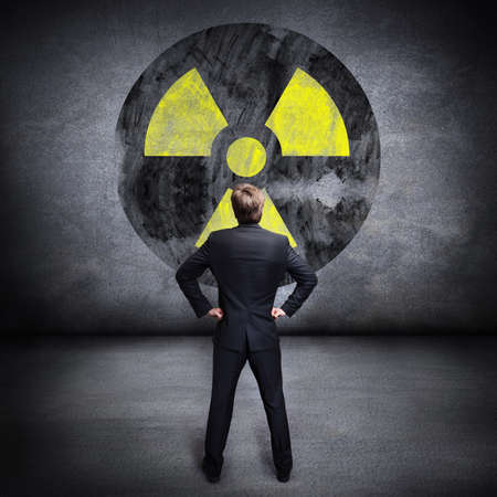 businessman standing in front of a big radiation sign photo