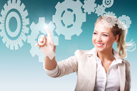 complex system: young businesswoman touching a virtual cogwheel in a more complex system, as a symbol for teamwork and motivation
