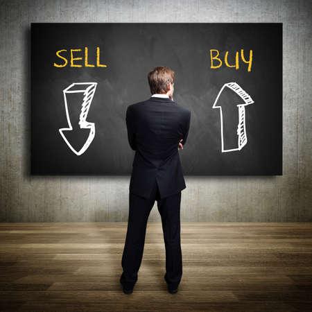 시도 칠판 앞에 서 사업가 구입 또는 판매 여부를 결정합니다