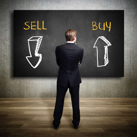 businessman standing in front of a blackboard trying to decide whether to buy or to sell