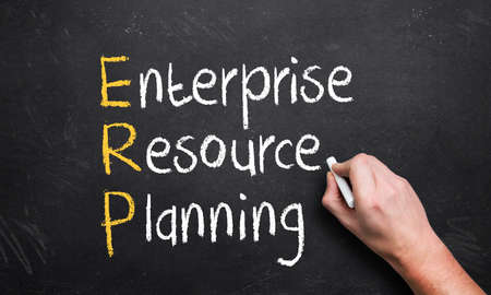 hand writing enterprise resource planning on a chalk board with the first letters in a different color photo