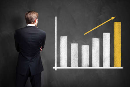 businessman in front of a growing graph photo