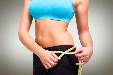 slim young woman measuring her waistline