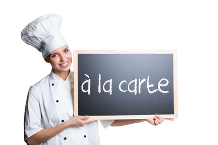 carte: young cook presenting a blackboard with the message ? la carte