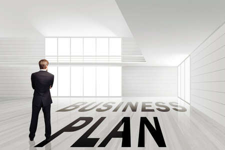 businessman standing in an empty office space with the message business plan on the ground