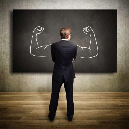 lideres: fuerte empresario de pie delante de una pizarra