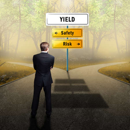 returns: businessman standing at a crossroad having to decide whether to take the risky or the safe way to yield Stock Photo
