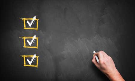 Tafel mit 3 geprüft Zeilen und einer Hand mit Kreide, zur Kundenbezogenheit mit eigenen Checklistenpunkte Standard-Bild