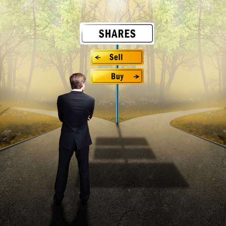 buy shares: businessman standing at a crossroad having to decide whether to sell or buy shares