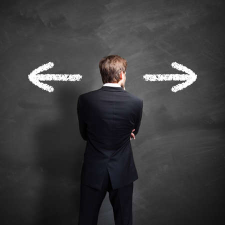 businessman has to decide which way to go