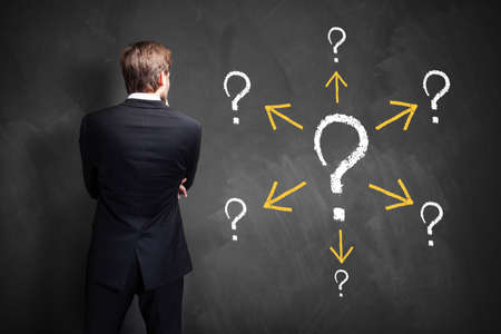 incertitude: businessman stands in front of a blackboard having many questions Stock Photo