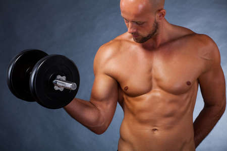 arm muscles: muscular man with a dumbbell during a workout