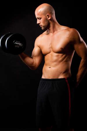 levantar pesas: hombre musculoso con una mancuerna durante un entrenamiento