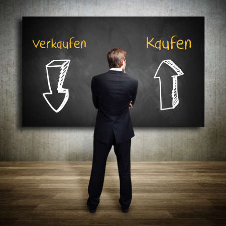 sell shares: businessman standing in front of a blackboard, having to choose what to do (with the words sell and buy in German) Stock Photo