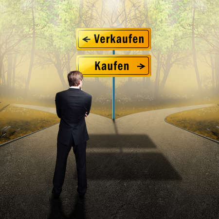 choose a path: businessman standing on a crossroad, having to choose the right path what to do (with the words sell and buy in German)