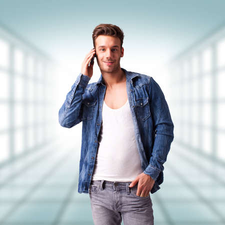facing right: handsome young man in jeans with a telephone