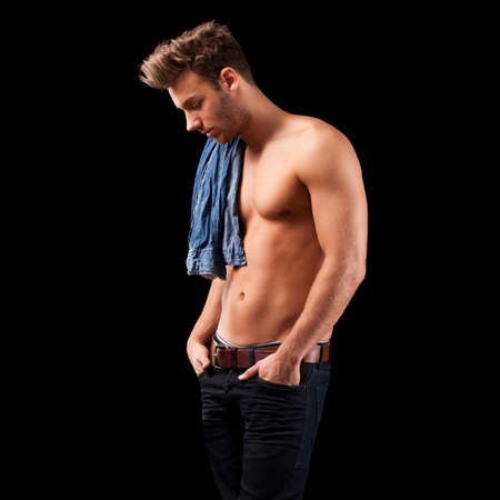 young man jeans: handsome young man in jeans on black background
