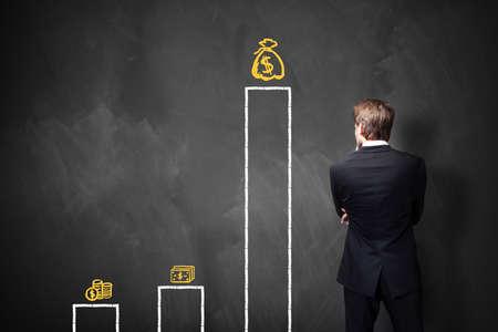 growth: hombre de negocios de pie delante de una pizarra con una tabla sobre los diferentes tipos de salarios Foto de archivo
