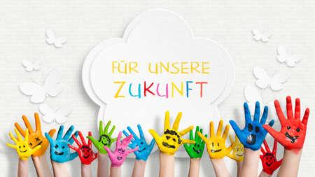 """독일어로 """"우리의 미래를 들어""""문장으로 장식 된 벽의 앞에 다채로운 칠한 손"""