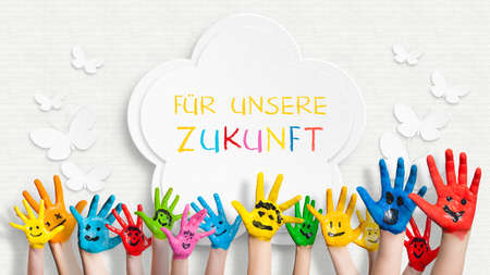 """frase: manos pintadas de colores en frente de una pared adornada con la frase """"Por nuestro futuro"""" en alem�n"""