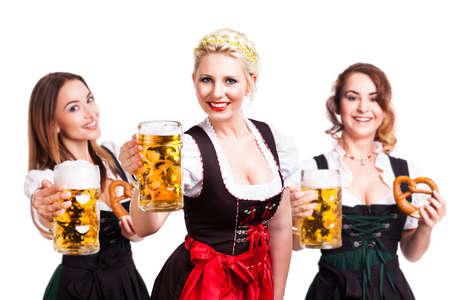 jovenes tomando alcohol: tres hermosas mujeres en dirndl tradicional bávaro con la cerveza y pretzel Foto de archivo