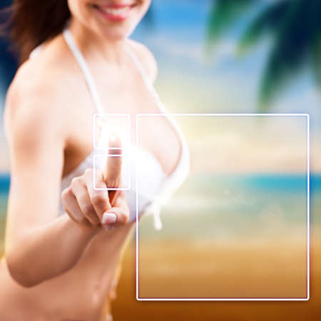 slender woman: attractive woman in beach wear using a touch interface