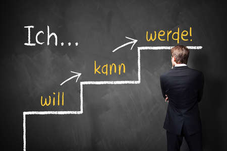 businessman stands in front of a blackboard with a motivational message in German photo