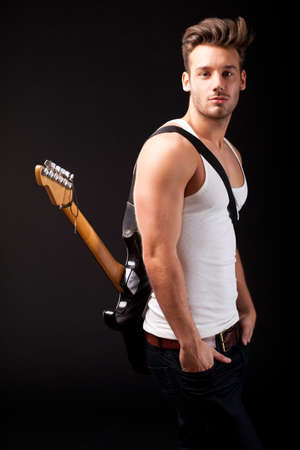 attractive man with a guitar on black background