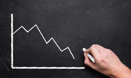 unacceptable: hand drawing a decreasing chart on a blackboard Stock Photo